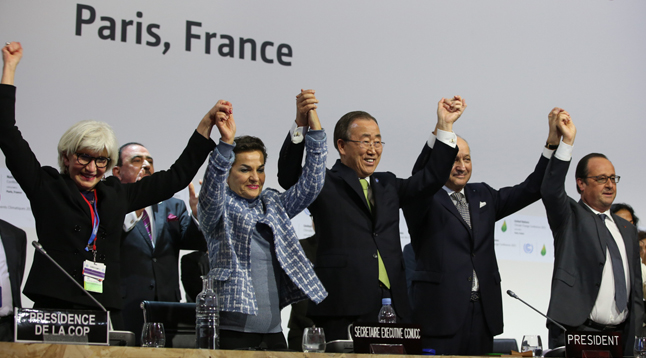 Delegates at COP21 raise hands in celebration of the Paris Agreement.