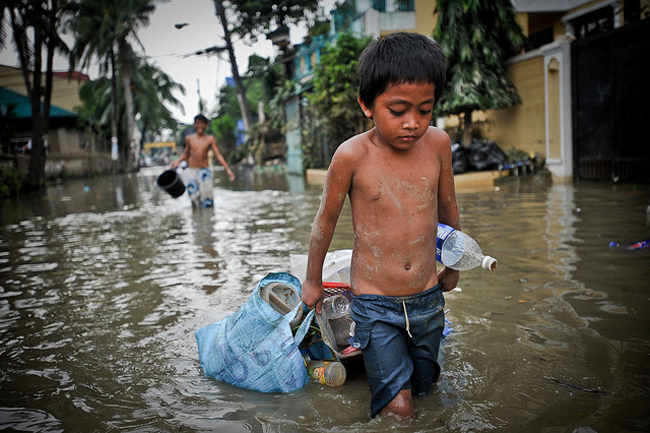 In the aftermath of Typhoon Ketsana (Ondoy), a boy drags some possessions through the flooded streets of Metro Manila.