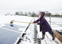 Girl brushing snow from a solar panel.