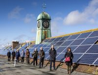 People on roof with solar panels.